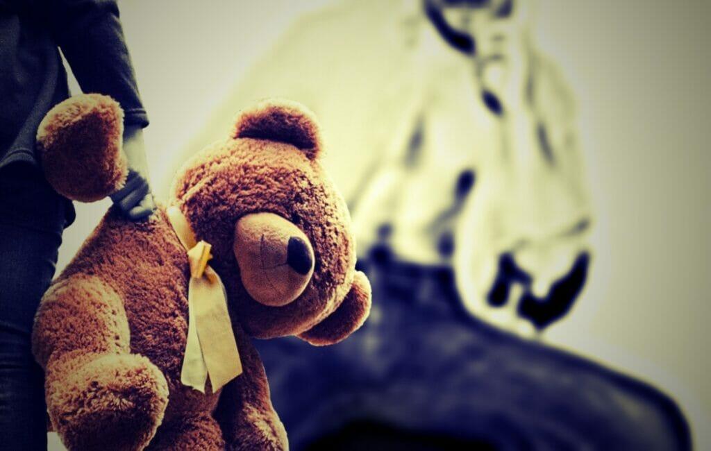 Kind mit Teddybären in der Hand. Im Hintergrund sieht man die Umrisse einer männlichen Person. Das Kind hat Angst vor Gewalt und Missbrauch.