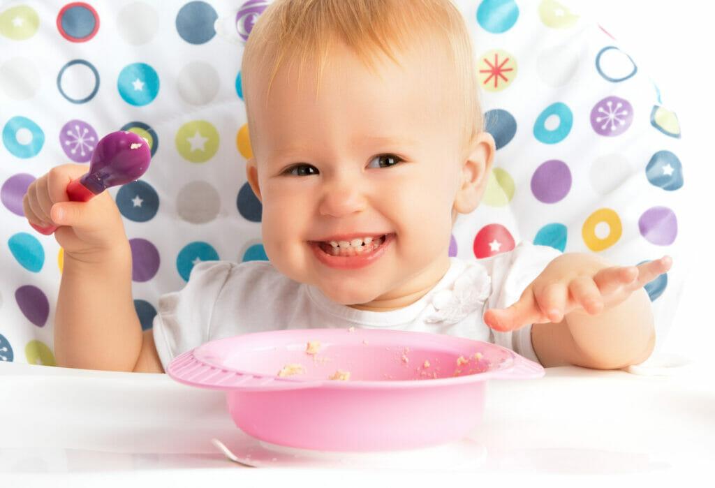 Baby hat einen Loeffel in der Hand und isst Brei