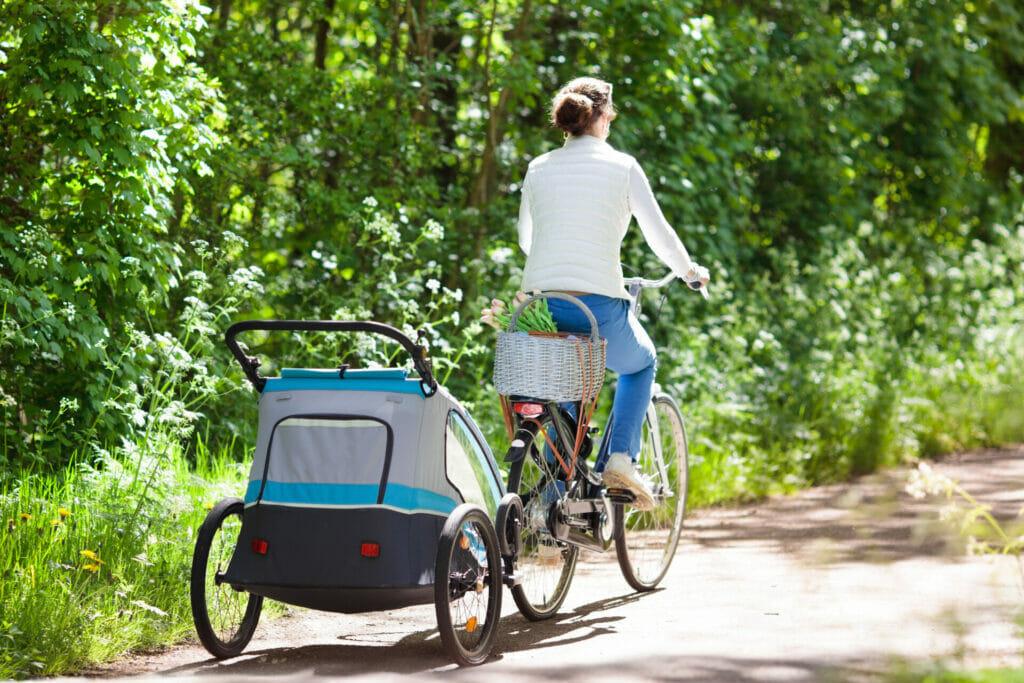 Eine Frau zieht mit ihrem Fahrrad einen Kinderfahrradanhänger