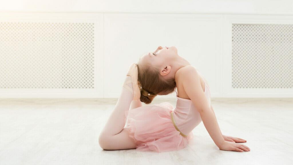 Ein kleines Mädchen mit einem rosa Tutu macht Ballett