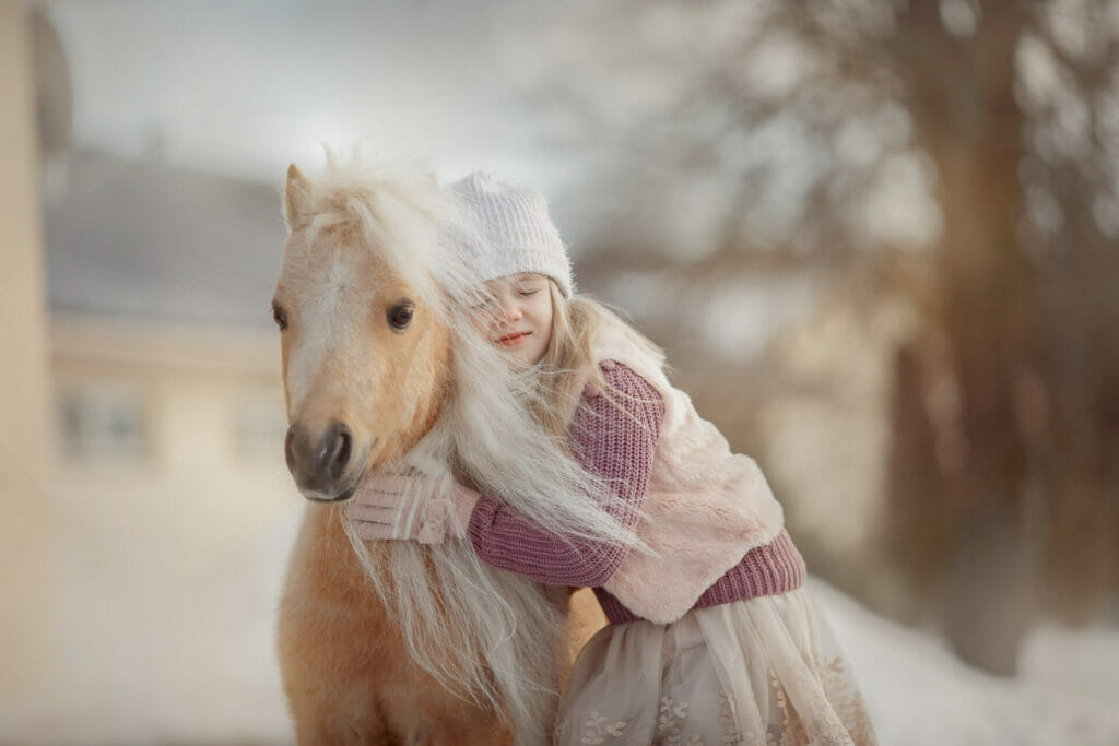 Ein Mädchen schmust mit einem Pony
