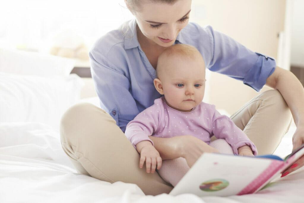 Eine Mutter schaut sich mit ihrem Baby ein Buch an
