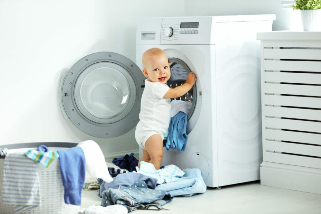 Baby raeumt Waesche in die Waschmaschine