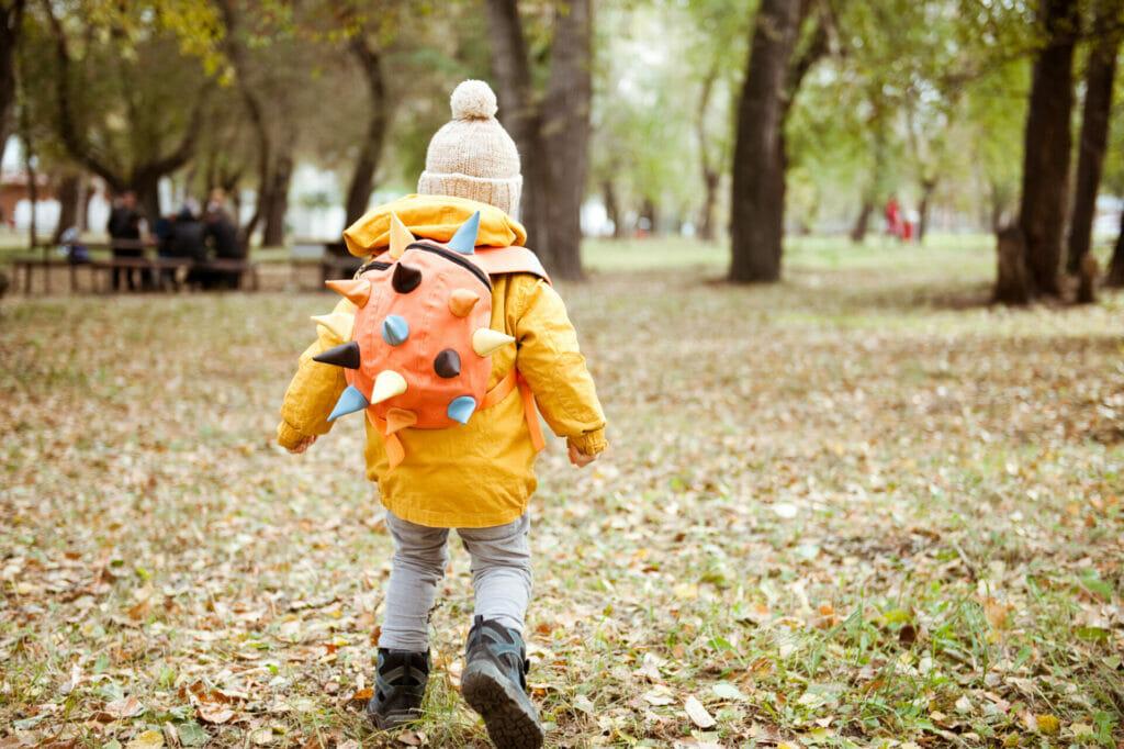 Ein kleines Kind läuft an einem Herbsttag mit einem Rucksack einen Weg entlang