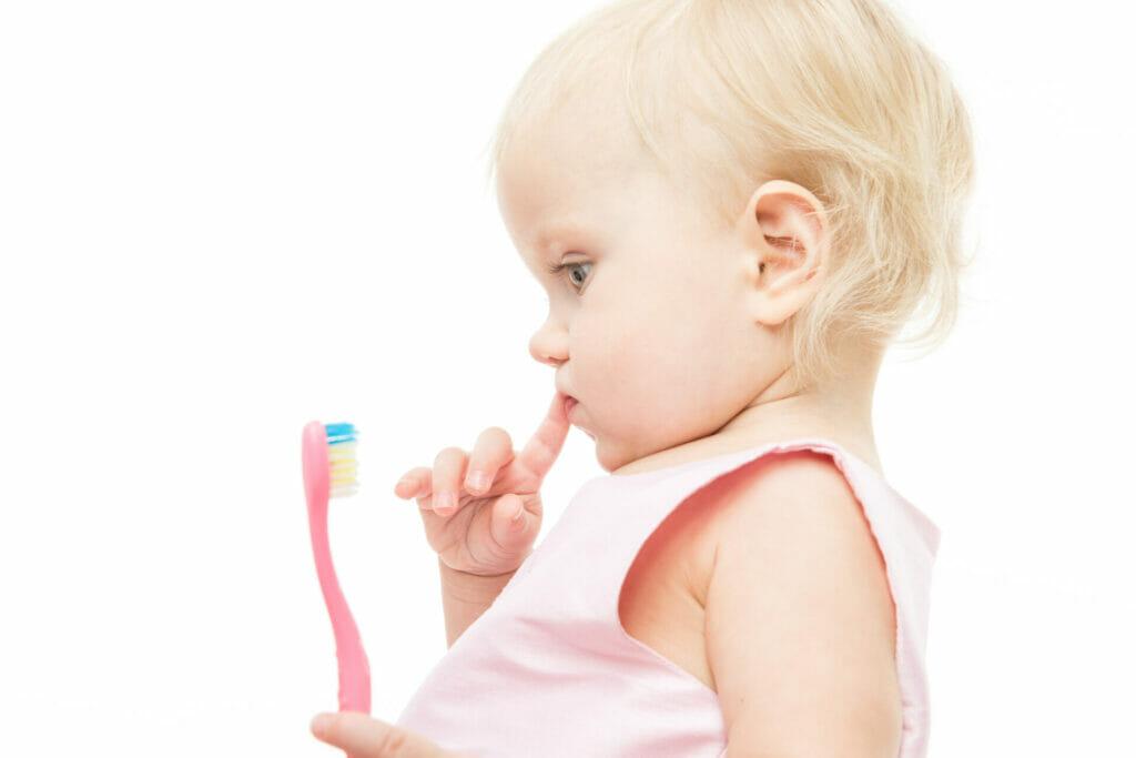 Kleines Mädchen hat eine Zahnbürste in der Hand