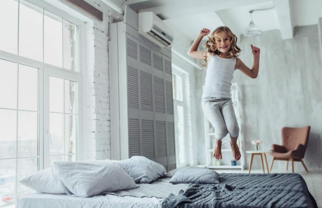 Mädchen hüpft auf einem Bett